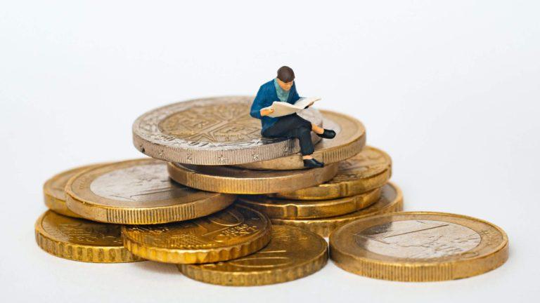 コインの上に座り新聞に集中する男性