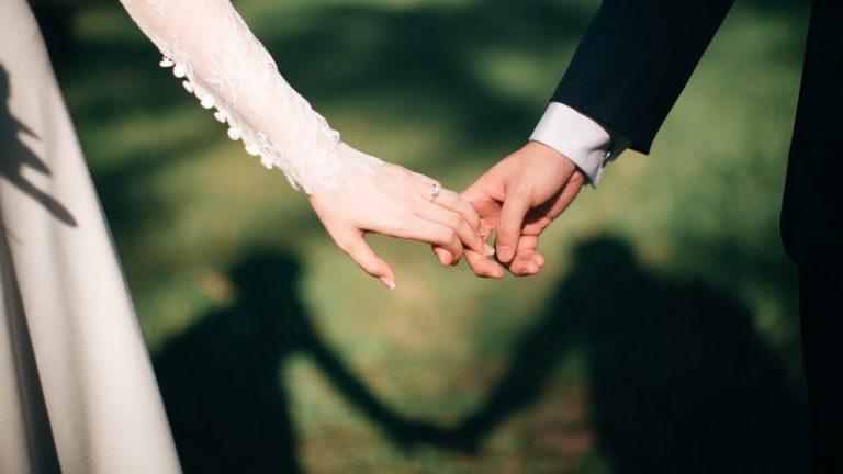 結婚式で手を繋ぐ男女と影